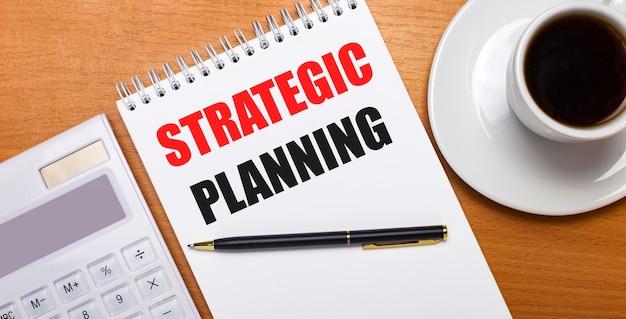 Sur une table en bois il y a une calculatrice, un stylo et un cahier blanc avec le texte planification stratégique