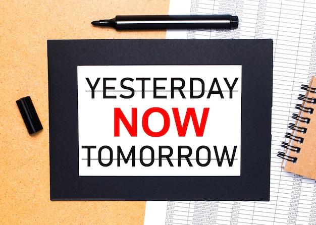 Sur une table en bois, il y a un marqueur noir ouvert, un bloc-notes marron et une feuille de papier dans un cadre noir avec le texte hier maintenant demain. vue d'en-haut.