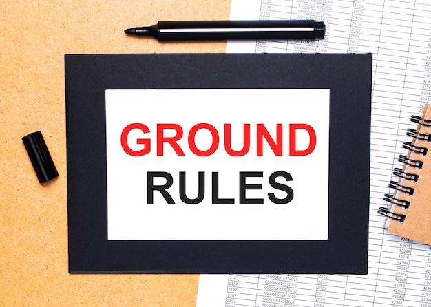 Sur une table en bois, il y a un marqueur noir ouvert, un bloc-notes marron et une feuille de papier dans un cadre noir avec le texte règles de terre