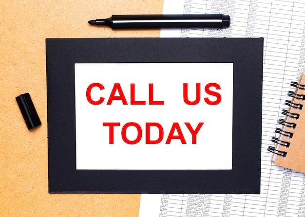 Sur une table en bois, il y a un marqueur ouvert noir, un bloc-notes marron et une feuille de papier dans un cadre noir avec le texte appelez-nous aujourd'hui. vue d'en-haut.