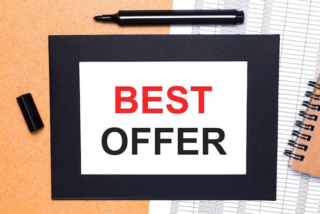 Sur une table en bois, il y a un marqueur ouvert noir, un bloc-notes marron et une feuille de papier dans un cadre noir avec le texte meilleure offre. vue d'en-haut.