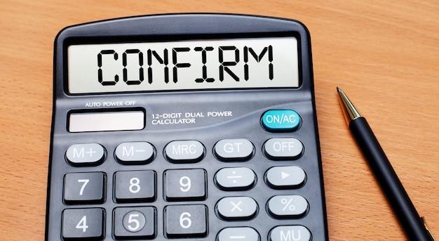 Sur une table en bois, il y a un stylo noir et une calculatrice avec le texte confirmer. concept d'entreprise