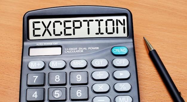 Sur une table en bois, il y a un stylo noir et une calculatrice avec le texte exception. concept d'entreprise
