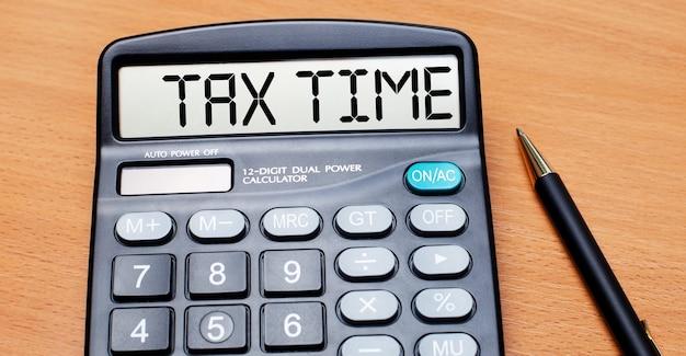 Sur une table en bois, il y a un stylo noir et une calculatrice avec le texte tax time. concept d'entreprise