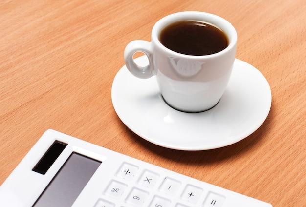 Sur une table en bois, il y a une tasse blanche avec du café et une calculatrice blanche. concept d'entreprise