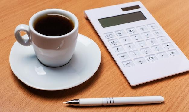 Sur une table en bois, il y a une tasse blanche avec du café, une calculatrice blanche et un stylo blanc. concept d'entreprise