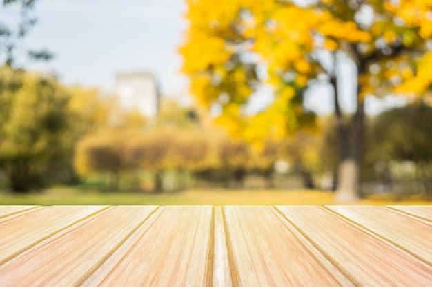 Table en bois jaune vide avec parc de la ville floue
