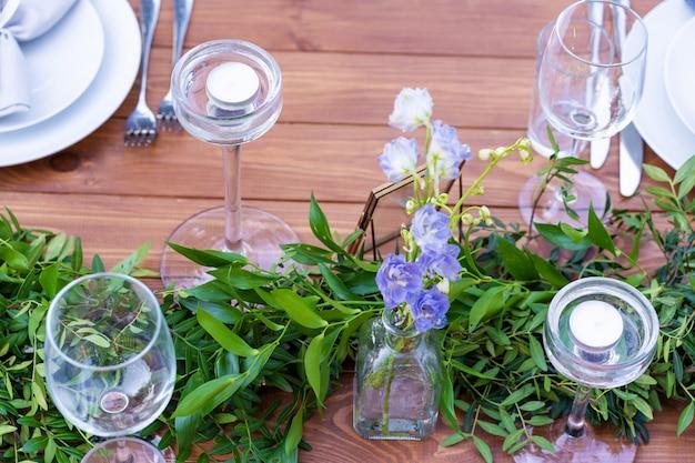 Table en bois joliment décorée dans un café d'été en plein air. décoration de table branche verte et fleurs fraîches
