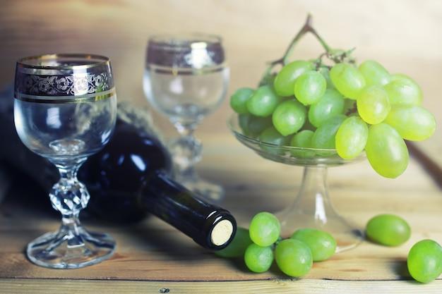 Table en bois avec livre de bouteille de vin et raisin