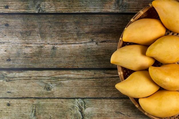 Table en bois de mangues fraîches jaune 0n. fruits tropicaux de mangue. mangues.