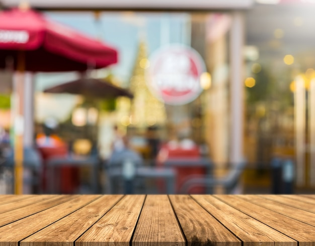 Table en bois marron devant un café.