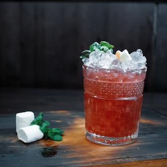 Sur la table en bois marron du café se trouve un cocktail rouge sucré avec l'ajout de: martini, vodka, tonic, glaçons et menthe fraîche. dégustation d'alcool. cocktail dans un verre vintage en cristal