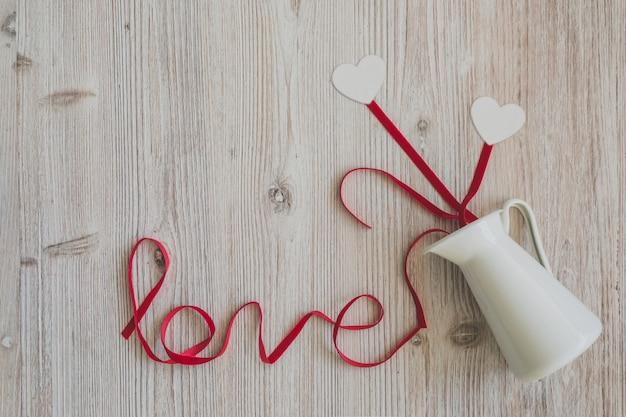 Table en bois avec le mot «amour» et un lanceur dont les coeurs sortent