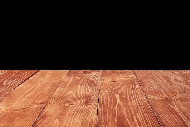 Table en bois naturel texturé vieilli vide sur fond noir pour présenter et monter vos produits et objets. utilisation de l'empilement de mise au point pour créer une profondeur de champ complète.