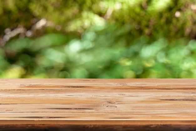 Table en bois naturel vierge sur un fond de feuilles vertes floues avec bokeh pour la démonstration et le montage de vos produits et objets.