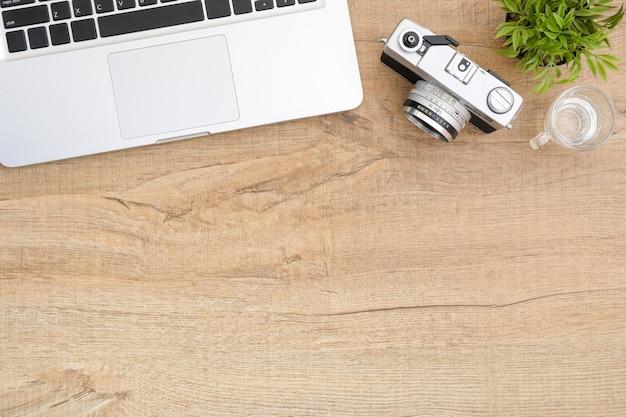 Table en bois avec ordinateur portable et appareil photo argentique.