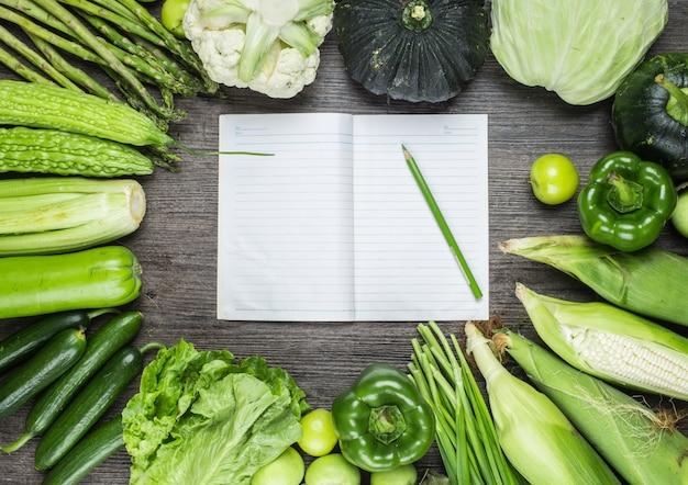 Table en bois avec un ordinateur portable et les légumes verts