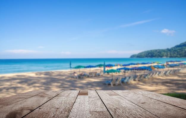 Table en bois sur un parasol flou et certaines personnes se détendent sur la plage de sable blanc et la mer bleue avec un ciel bleu