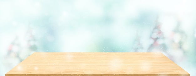 Table en bois de perspective avec arbre de noël flou décorer la lumière de la chaîne et le bokeh bleu