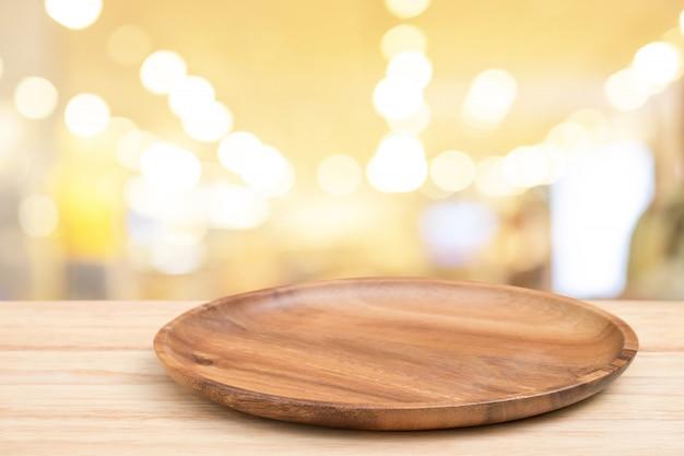 Table en bois de perspective et plateau en bois sur le dessus sur fond clair flou bokeh.