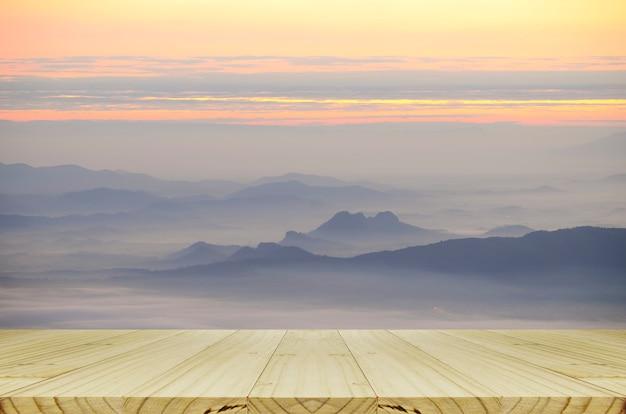 Table en bois perspective avec vue sur la montagne et la brume.