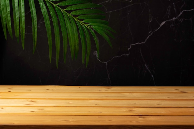 Table en bois pour l'affichage et la présentation du produit, l'été et l'arrière-plan des feuilles de palmier