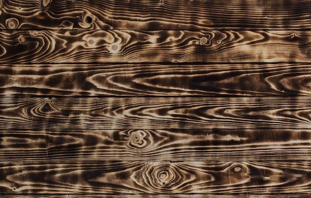 Table en bois rayé foncé brûlant
