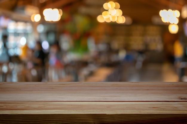 Une table en bois sur un restaurant flou fond