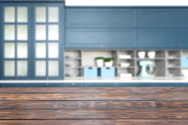 Table en bois rustique au premier plan avec armoire de cuisine bleue à l'arrière-plan flou.