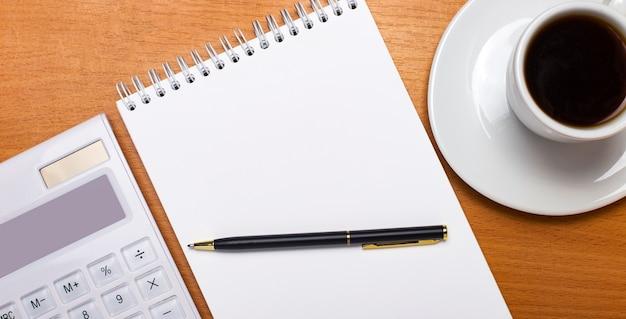 Sur une table en bois se trouve une calculatrice blanche, une tasse de café blanche, un stylo et un cahier blanc vierge avec un emplacement pour insérer du texte. modèle. concept d'entreprise