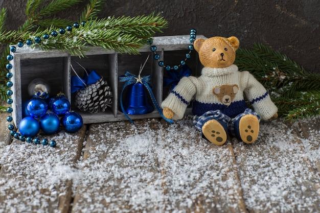 Sur la table en bois se trouve un vieil ours (jouet) et un décor d'hiver