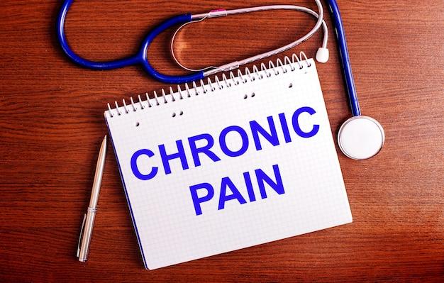 Sur une table en bois se trouvent un stylo, un stéthoscope et un cahier portant la mention douleur chronique.