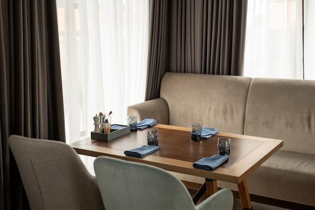 Table en bois servie entourée d'un confortable canapé en velours doux et armchars par fenêtre avec des rideaux en mousseline blanche