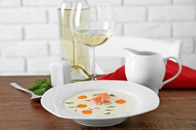 Table en bois servie avec une savoureuse soupe à la crème de saumon, du vin et du citron dessus, gros plan