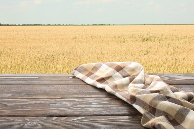 Table en bois avec serviette contre champ. concept d'agriculture