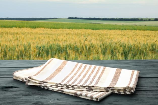 Table en bois avec serviette contre champ. la saison des récoltes