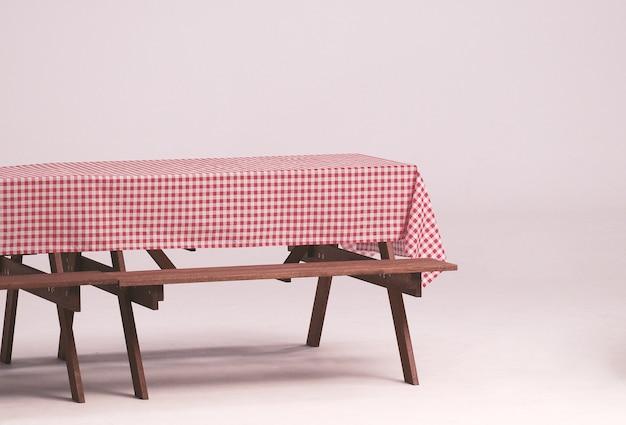 Table en bois et serviette rouge pour fête en plein air et fond blanc.