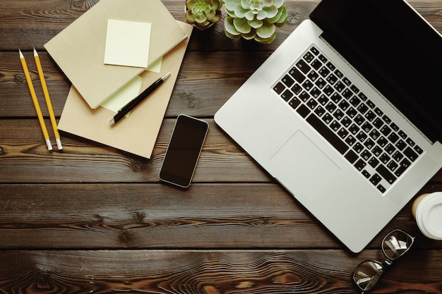 Table en bois sombre avec ordinateur portable, vue de dessus du bloc-notes
