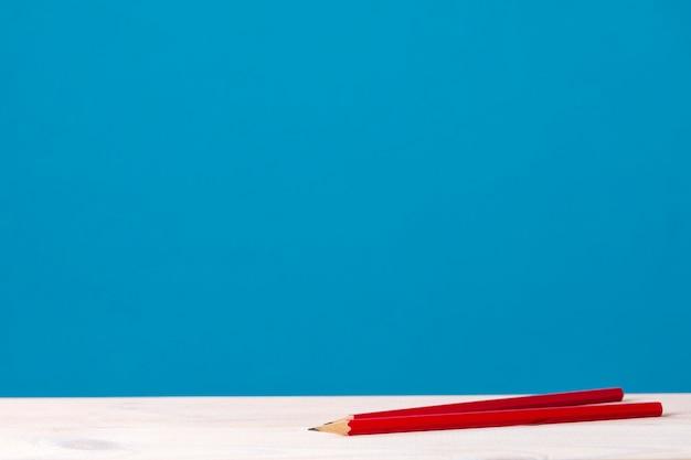 Sur une table en bois sont deux crayons rouges