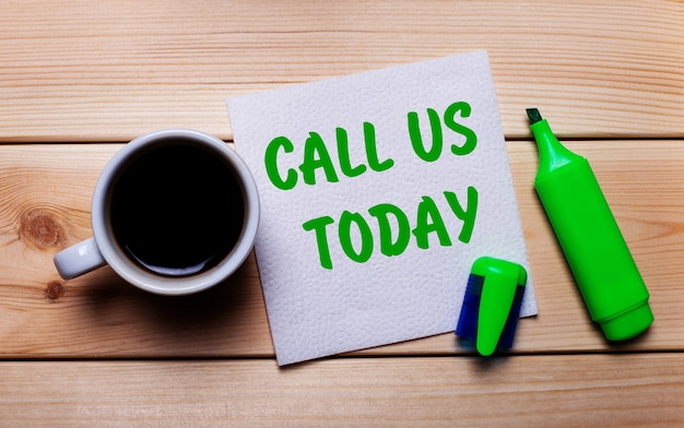 Sur une table en bois, une tasse de café, un marqueur vert et une serviette avec le texte appelez-nous aujourd'hui