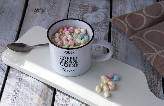 Sur une table en bois une tasse de chocolat chaud et de guimauves