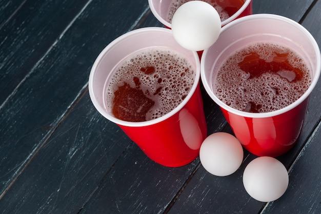 Table en bois avec des tasses rouges et une boule pour beer pong