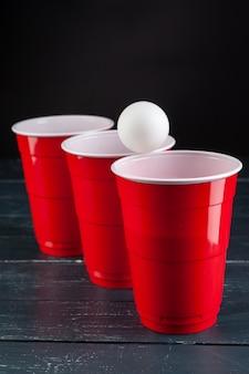 Table en bois avec tasses rouges et boule pour bière-pong