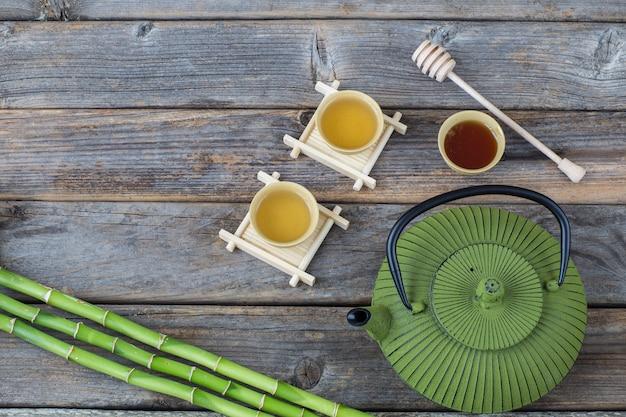 Sur une table en bois, thé vert dans des bols, miel, bambou, théière