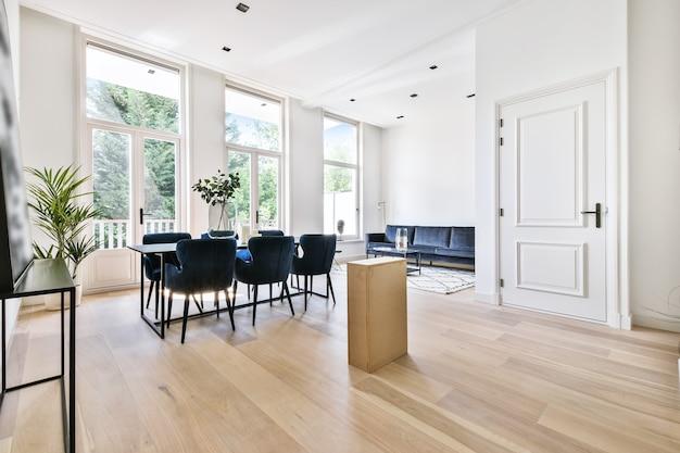 Table en bois avec vase et chaises dans la salle à manger lumineuse à la maison