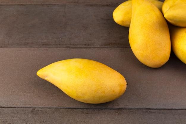 Table en bois véritable de mangues fraîches jaune. fruits tropicaux de mangue. mangues.