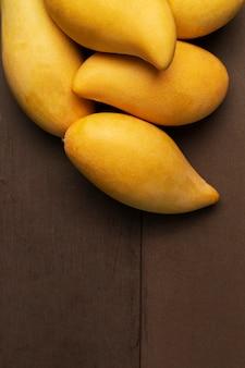 Table en bois véritable de mangues fraîches jaune. fruits tropicaux de mangue.