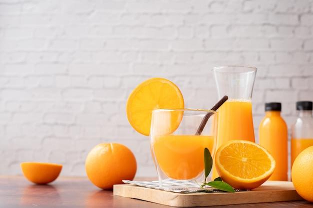 Table en bois avec des verres de jus d'orange fraîchement pressé, sans sucre ajouté.