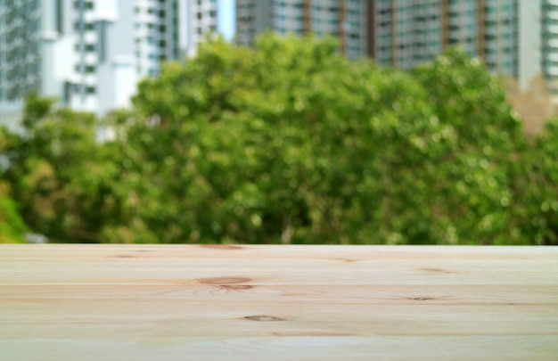 Table en bois vide sur le balcon avec feuillage vert flou et bâtiment moderne en arrière-plan