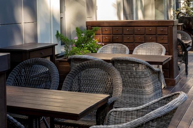 Table en bois vide et chaises en osier dans un café en plein air.
